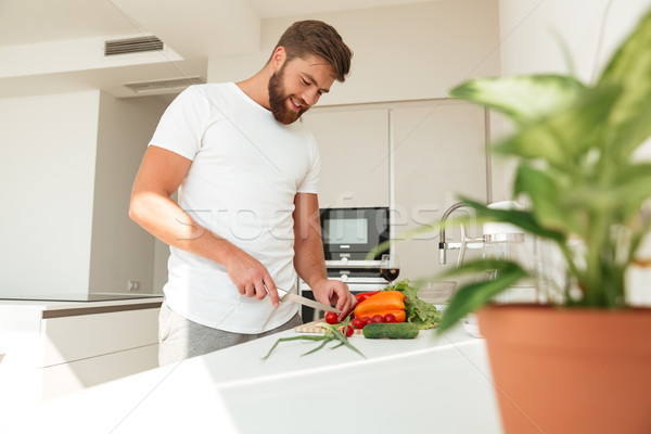 Side view of casual bearded man cuts vegetables Stock photo © deandrobot