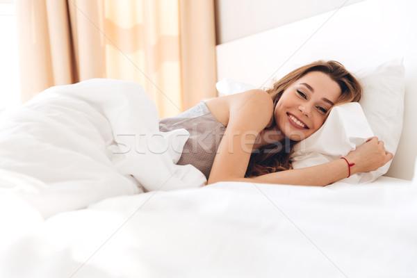 Szczęśliwy dość pani leży bed Zdjęcia stock © deandrobot