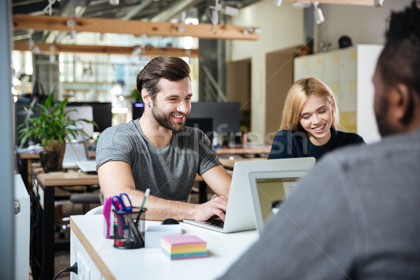 Smiling young colleagues sitting in office coworking. Stock photo © deandrobot