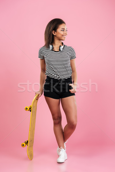 Pretty young african lady standing isolated over pink background Stock photo © deandrobot