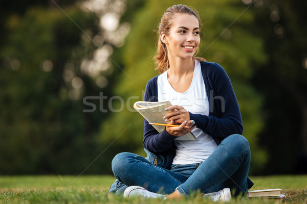 Portrait of a smiling pretty schoolgirl holding textbook Stock photo © deandrobot