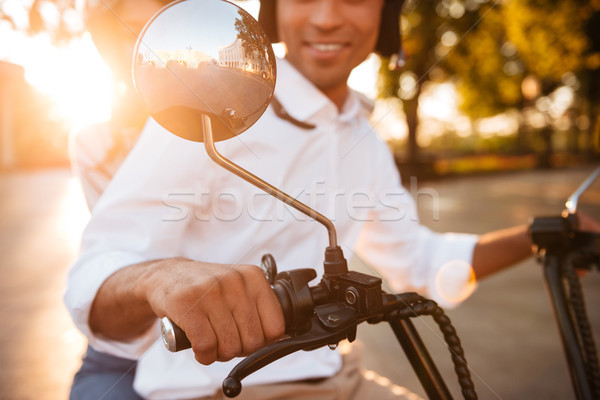 Cropped image of happy african couple rides on modern motorbike Stock photo © deandrobot