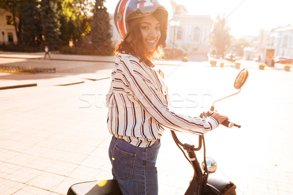 Side view of carefree african woman rides on modern motorbike Stock photo © deandrobot