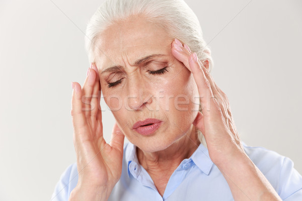 Close-up portrait of elderly lady with headache Stock photo © deandrobot