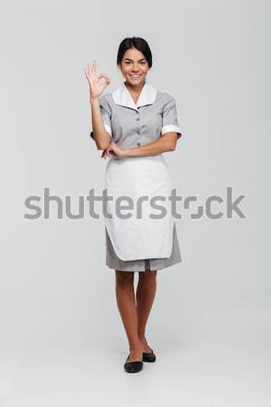Full length portrait of smiling beautiful housekeeper in uniform Stock photo © deandrobot