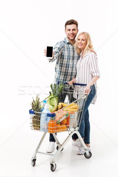 Teljes alakos portré pár mutat képernyő mobiltelefon Stock fotó © deandrobot