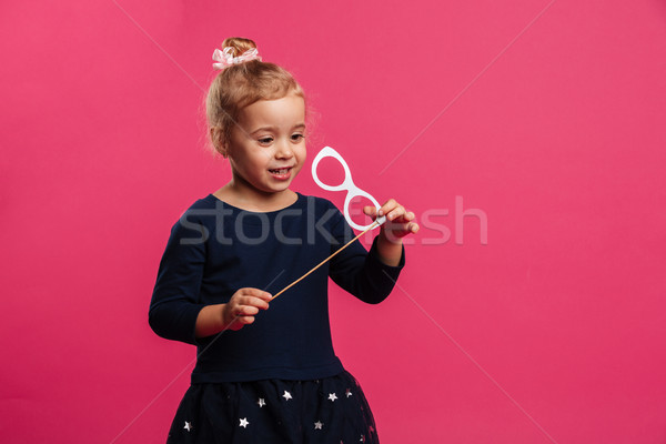 Happy young blonde girl playing with paper eyeglasses in studio Stock photo © deandrobot