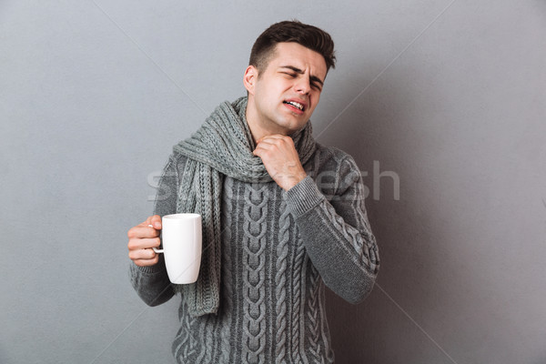 Displeased illness man wearing warm scarf holding hot tea. Stock photo © deandrobot