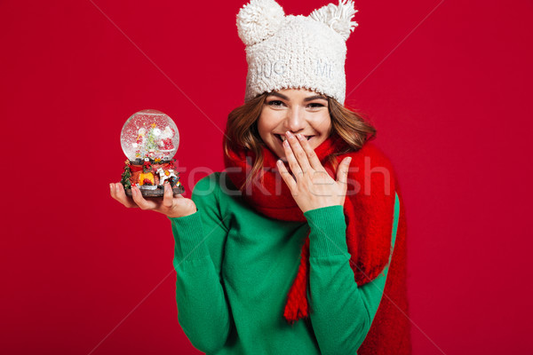 Young pretty lady wearing hat and scarf holding christmas toy Stock photo © deandrobot