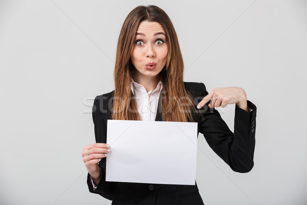 Funny lady grimacing and pointing at white sheet isolated Stock photo © deandrobot