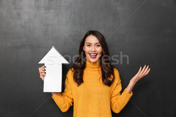 Happy brunette woman in sweater pointing with paper arrow up Stock photo © deandrobot