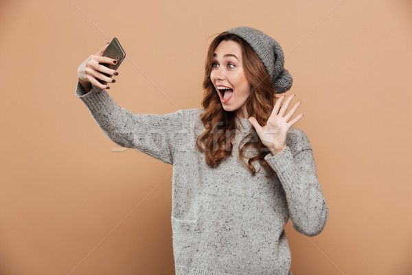 Portrait of young smiling girl in warm clothes showing HI while  Stock photo © deandrobot