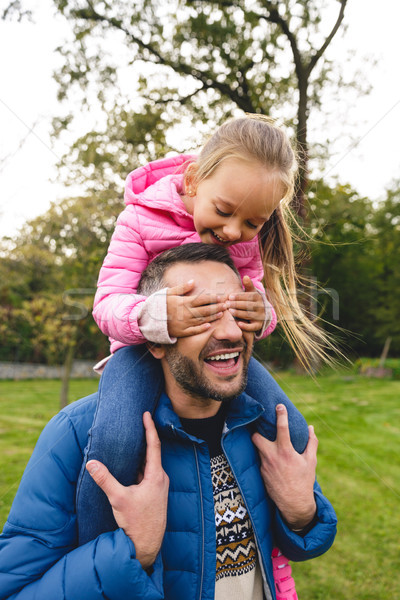 Stock photo: Smiling little girl riding on father's back in the park