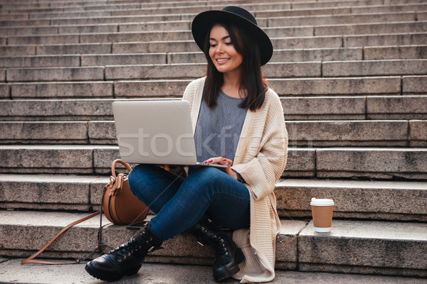 Stock photo: Portrait of a smiling pretty woman using laptop computer