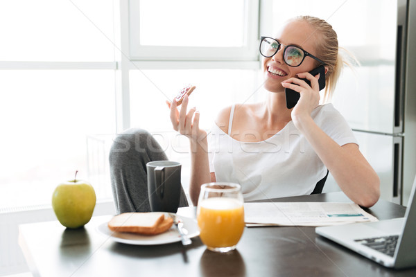 Smiling lady talking on smartphone and working while have breakfast Stock photo © deandrobot