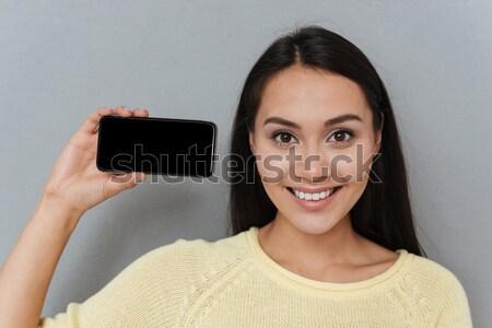 Derűs nő piros ajkak mutat kirakat mobiltelefon Stock fotó © deandrobot