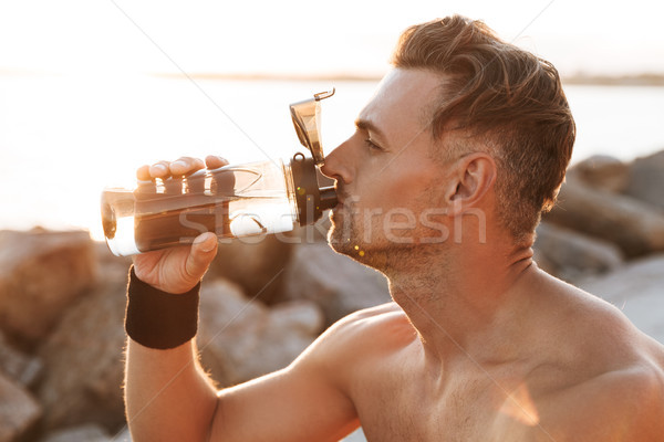 Close up portrait of a handsome shirtless sportsman Stock photo © deandrobot