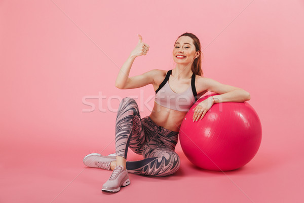 Happy sportswoman sitting on the floor with fitness ball Stock photo © deandrobot