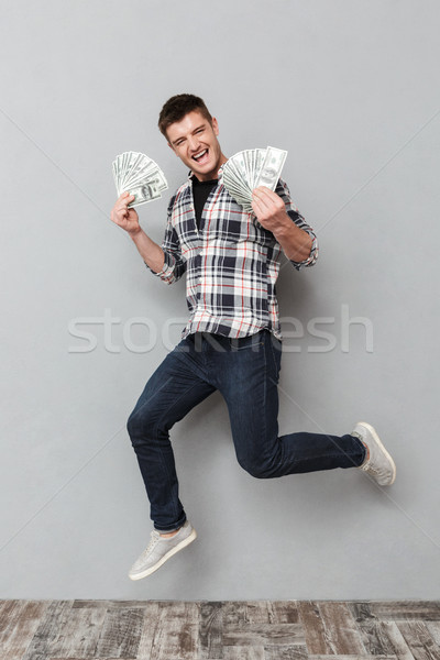 Full length portrait of a happy young man Stock photo © deandrobot