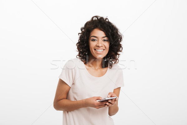 Happy woman 20s with curly hair wearing basic t-shirt holding mo Stock photo © deandrobot