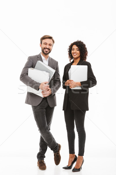Full length portrait of a business couple holding folders Stock photo © deandrobot