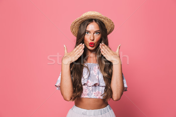 Portrait of glamour woman 20s wearing straw hat putting lips tog Stock photo © deandrobot