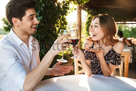 Loving couple sitting in cafe by dating drinking wine Stock photo © deandrobot