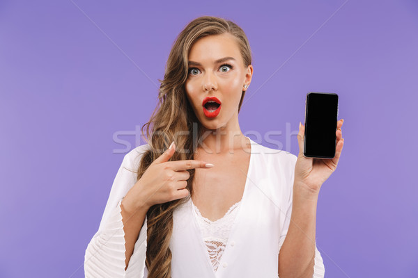 Portrait of a surprised young woman in white dress Stock photo © deandrobot