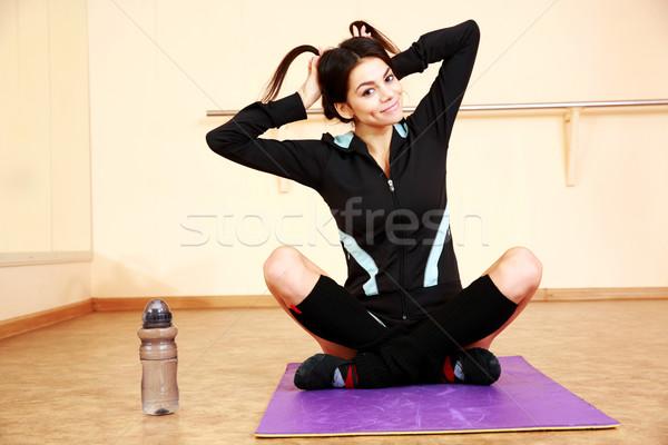 Genç komik uygun kadın oturma yoga mat Stok fotoğraf © deandrobot