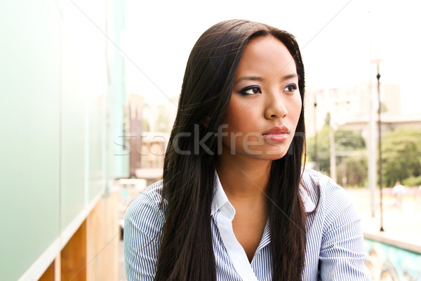 Portrait of an attractive asian business woman day dreaming  Stock photo © deandrobot