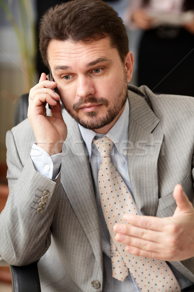 Portrait of a mature business man screaming in his cellphone in office environment Stock photo © deandrobot