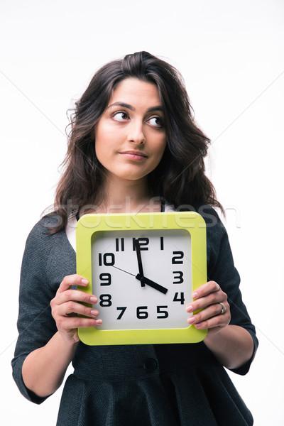 Pensive businesswoman holding clock Stock photo © deandrobot