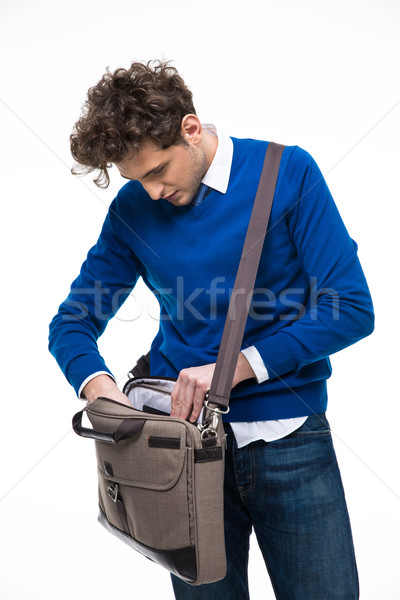 Young businessman searching documents in his bag Stock photo © deandrobot