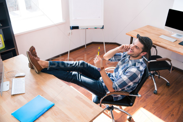 Businessman talking on the phone in office Stock photo © deandrobot