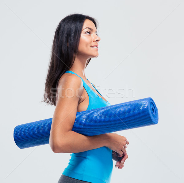 Happy sports woman holding yoga mat  Stock photo © deandrobot