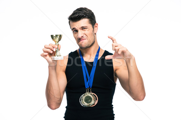 Stock photo: Sports man showing small winners cup