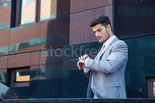 üzletember néz karóra kint irodaház város Stock fotó © deandrobot