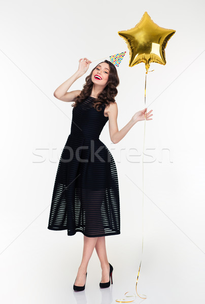 Happy woman with birthday hat prop and star shaped balloon Stock photo © deandrobot