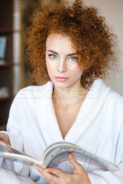 Lovely curly young woman in white bathrobe with magazine Stock photo © deandrobot