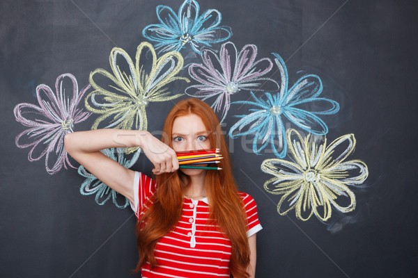 Wondered woman covered face with colorful pencils standing over chalkboard  Stock photo © deandrobot