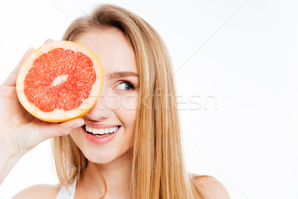 Woman holding slice of grapefruit Stock photo © deandrobot