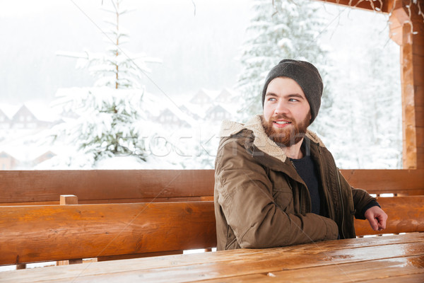 Bearded man sitting and smiling in wintertime outdoors Stock photo © deandrobot
