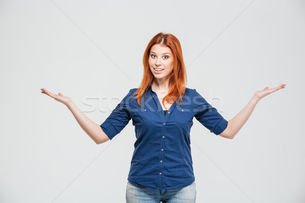 Beautiful smiling woman standing annd holding copyspace on both palms Stock photo © deandrobot