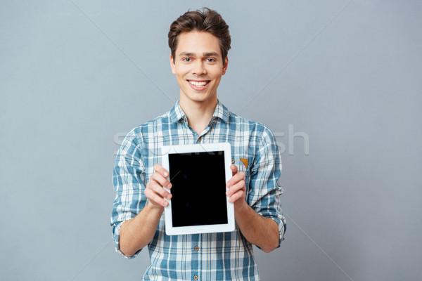 Glimlachend man tonen scherm toevallig Stockfoto © deandrobot