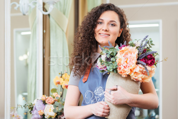 Cheerful woman florist holding vase with beautiful flowers in shop Stock photo © deandrobot