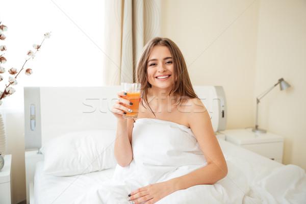 笑顔の女性 オレンジジュース ベッド ホーム 見える ストックフォト © deandrobot