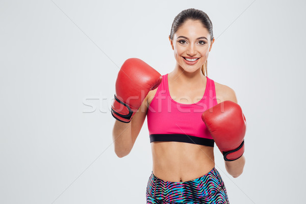 Smiling woman in boxing gloves looking at camera Stock photo © deandrobot