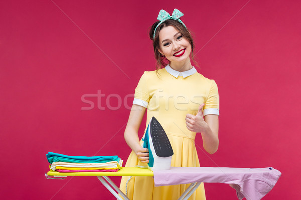 Happy lovely pinup girl ironing clothes and showing thumbs up Stock photo © deandrobot