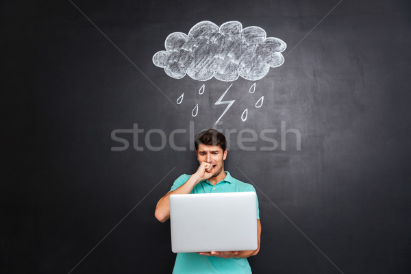 Nervous young man looking at pc computer with chalk blackboard Stock photo © deandrobot