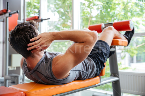 Young man doing bench press workout at the gym Stock photo © deandrobot